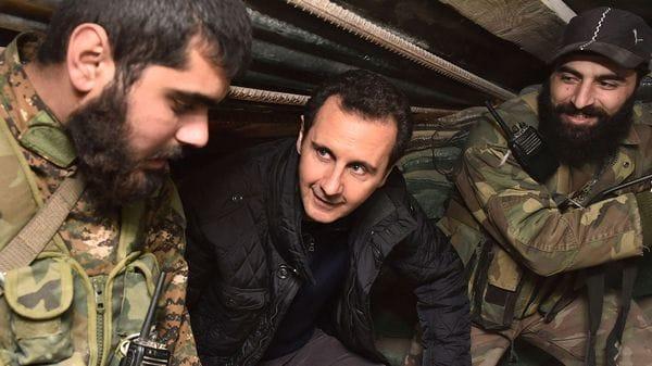 El presidente sirio, Bashar al Assad, junto a dos soldados durante una visita a Jobar, al noreste deDamasco (Reuters)