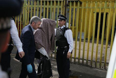 La policía de Londres custodia a una persona que se cubre el rostro luego de allanar su domicilio dentro de las investigaciones por el atentado del 3 de junio.
