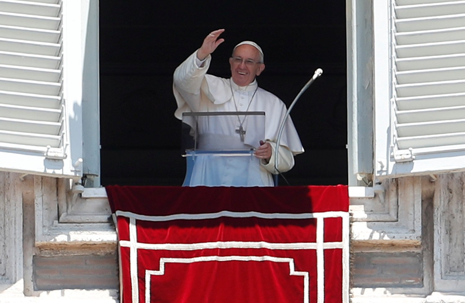 Pope Francis waves during his Sunday Angelus prayer in Saint Peter