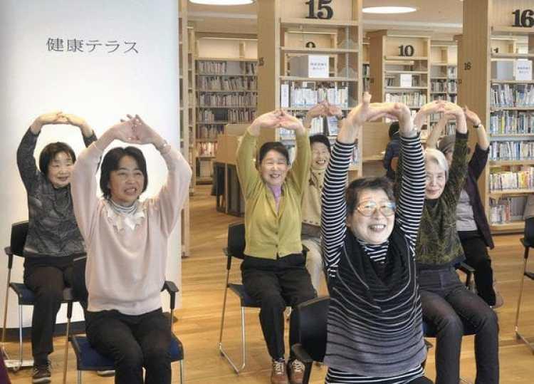 Un grupo de mujeres participan en una sesión de fitness rodeadas de estanterías con libros sobre salud y estilo de vida saludable en la biblioteca de Yamato, en la Prefectura Kanagawa, en Japón. (The Yomiuri Shimbun)