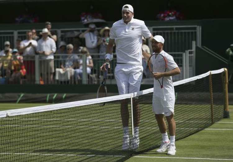 La diferencia de altura entre John Isner y Dudi Sela no pasó inadvertida(AP Photo/Tim Ireland)