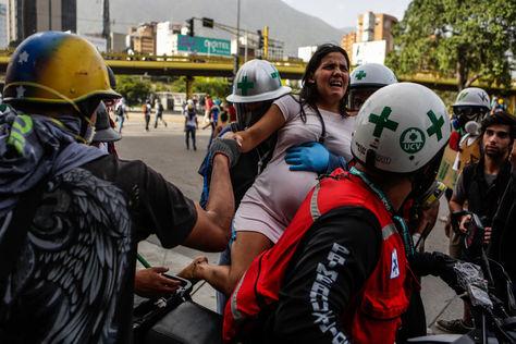 """Personal médico auxilia a una persona afectada por los gases lacrimógenos durante el """"trancazo"""" en Caracas. Foto: EFE"""
