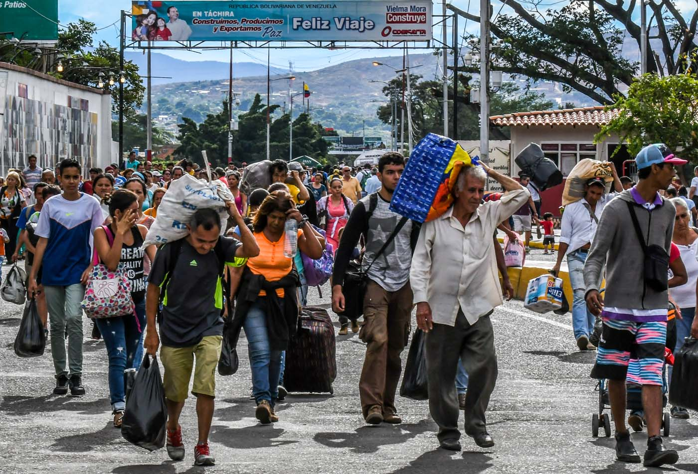 Venezuelan citizens cross the Simon Bolivar international bridge from San Antonio del Tachira, Venezuela to Cucuta, Norte de Santander Department, Colombia, on July 25, 2017. Some 25.000 Venezuelans cross to Colombia and return to their country daily with food, consumables and money from ilegal work, according to official sources. Also, there are 47.000 Venezuelans in Colombia with legal migratory status and another 150.000 who have already completed the 90 allowed days and are now without visa. / AFP PHOTO / Luis Acosta