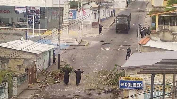 Los dos sacerdotes intentan mediar con las fuerzas de seguridad en las calles de Tovar (@Ciudad360Ve)