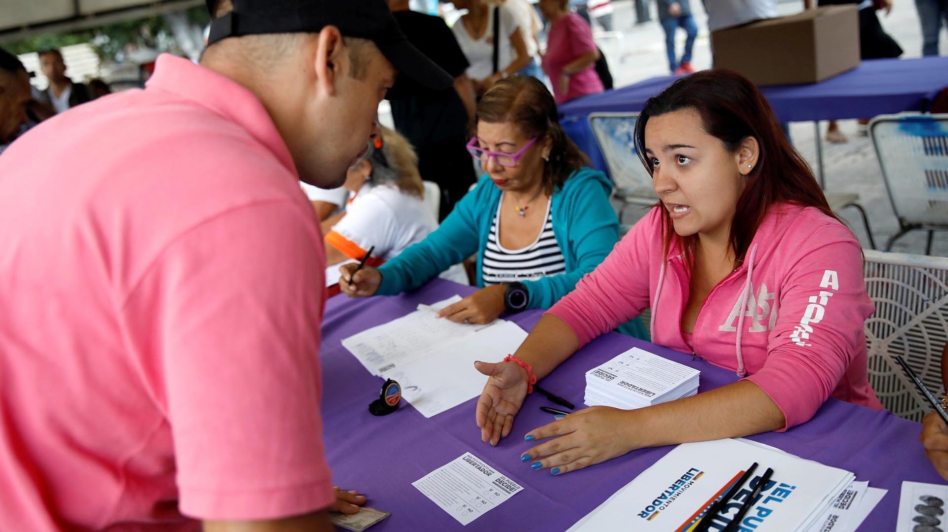 Una mujer explica el funcionamiento de la consulta popular del 16 de julio (Reuters)