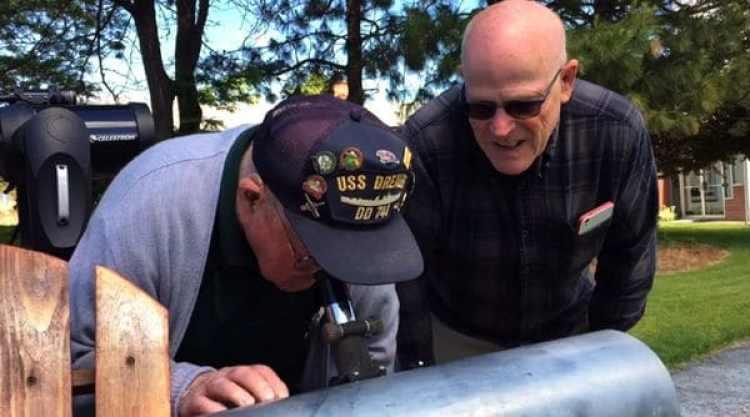 Esta imagen tomada de un video muestra a Gene Brick, de 92 años, y a su hijo, Bartt Brick, mirando a través de un telescopio que fabricaron juntos en 1964, en Madras, Oregon, el 12 de junio de 2017. Padre e hijo tienen previsto seguir juntos el eclipse solar del 21 de agosto de 2017 en Oregon