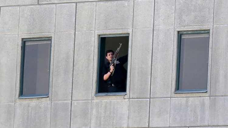 Un hombre armado mira desde una de las ventanas del Parlamento de Irán (AP)