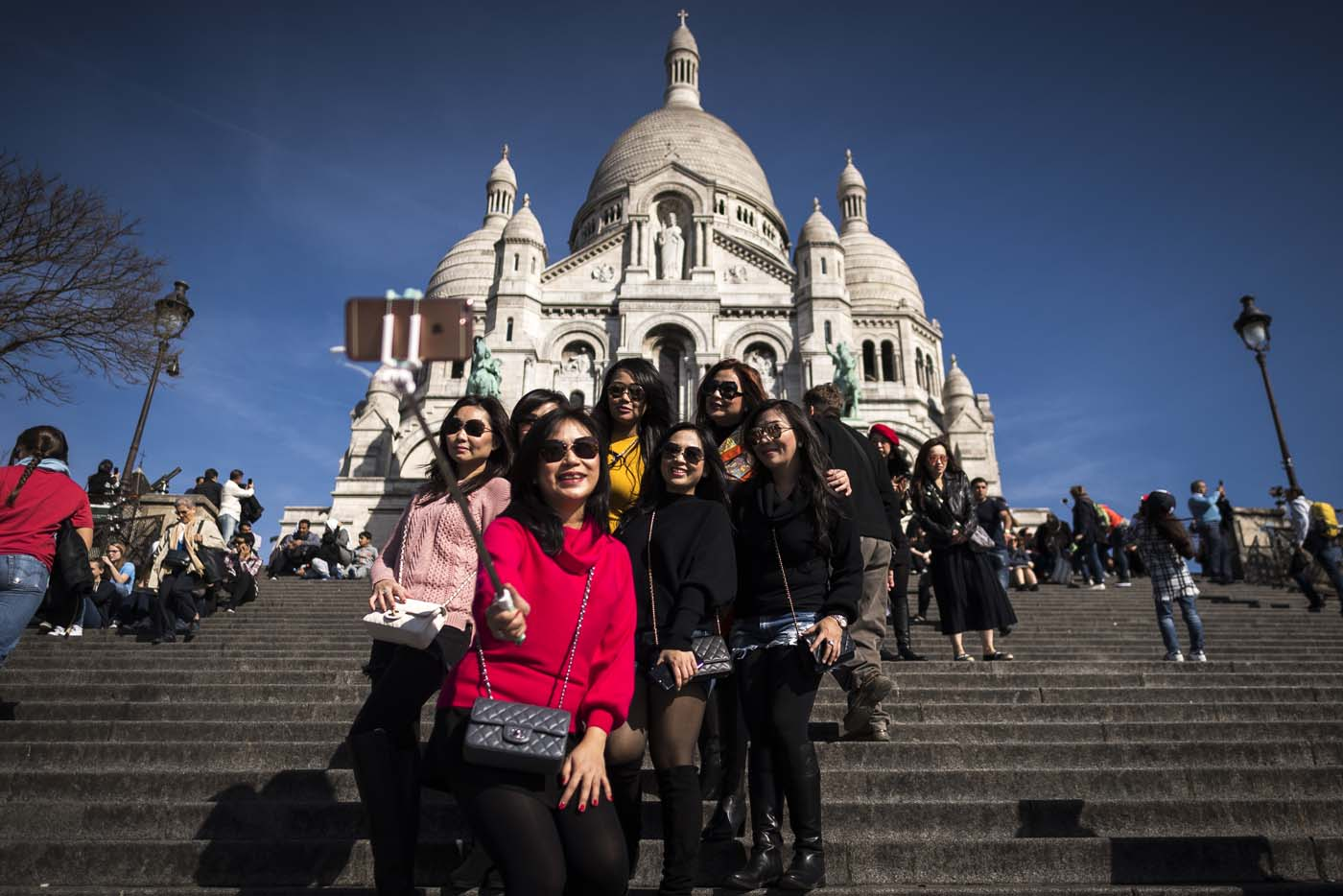 (FILES) This file photo taken on March 30, 2017 shows tourists taking selfie pictures in front of the Sacre Coeur basilica ontop of the Paris landmark district of Montmartre in Paris. After a decline in 2016 due to the terror attacks in Paris and Nice, tourism in Paris and Ile de France is in much better shape in the first half of 2017, with 1,5 million tourists and 3,3 million overnight stays more than a year ago. / AFP PHOTO / Lionel BONAVENTURE