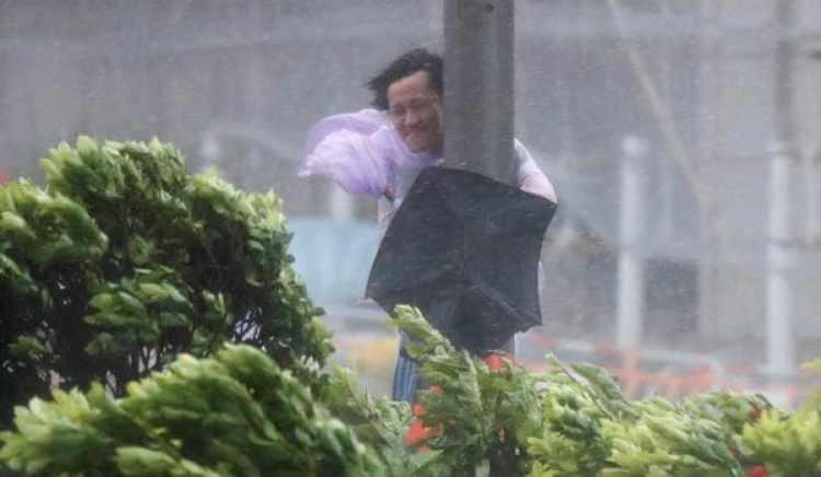 Un hombre se sostiene de un poste ante las ráfagas de viento en Hong Kong (Reuters)
