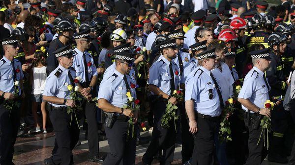 Varios policías llevanflores en honor a la víctimas del ataque terrorista mientras participan de la manifestación