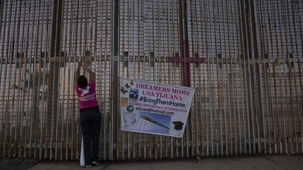 Una mujer cuelga una pancarta en la pared entre México y Estados Unidos durante una protesta contra el fin del programa DACA en Playas de Tijuana, Baja California