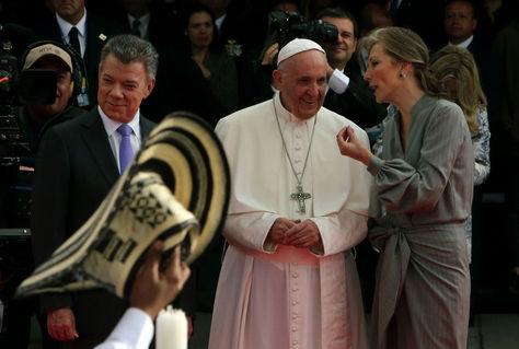 El papa Francisco (c), acompañado del presidente de Colombia, Juan Manuel Santos (i), y la primera dama colombiana María Clemencia de Santos (d), observa la presentación de un grupo de danza folclórica durante su recibimiento a la base aérea de Catam. Foto. EFE