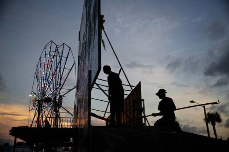 Trabajadores desarman las instalaciones de un parque de diversiones en Daytona Beach, Florida (AP Photo/David Goldman)