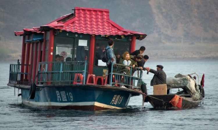 Un hombre le vende productos norcoreanos a turistas chinos desde un barco en el río Yalu cerca de Sinuiju, frente a la ciudad fronteriza china de Dandong, el 15 de abril de 2017. (AFP)