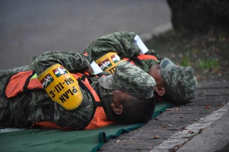 Agotados tras una larga noche, soldados toman un descanso entre los rescates (AFP)