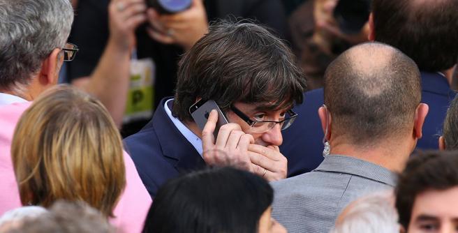 Carles Puigdemont hablando por teléfono junto a un guardaespaldas en la manifestación de este sábado