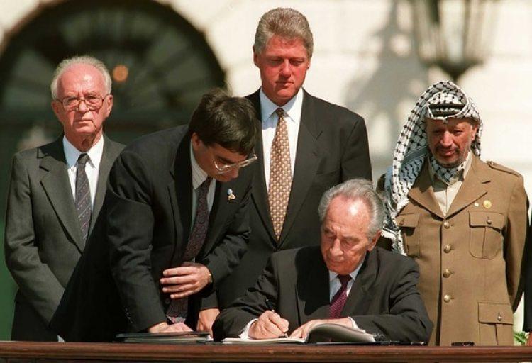 Shimon Peres firma los acuerdos de Oslo. Detrás: Isaac Rabin, Bill Clinton y Yaser Arafat (AFP)