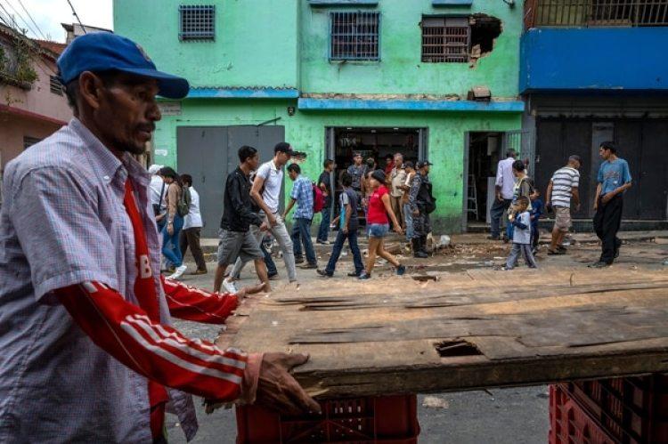 Un grupo de personas caminan frente a una licorera que fue saqueada en horas de la madrugada en el sector La Vega en Caracas (Venezuela).(EFE/Miguel Gutiérrez)