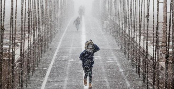 Peatones se protegen de la nieve y del viento mientras cruzan el puente de Brooklyn durante una tormenta de viento y nieve en Nueva York (Estados Unidos), hoy 4 de enero de 2017.EFE