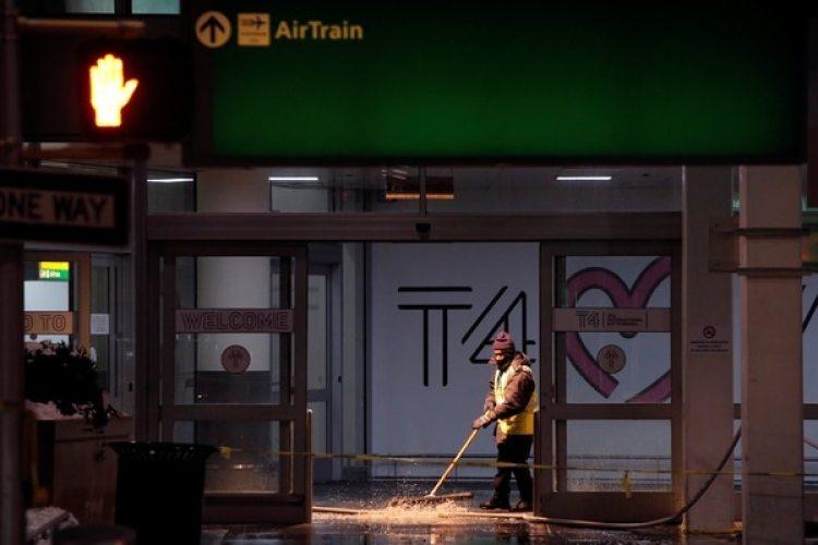 Un trabajador saca el agua de la terminal 4 del aeropuerto (REUTERS/Andrew Kelly)