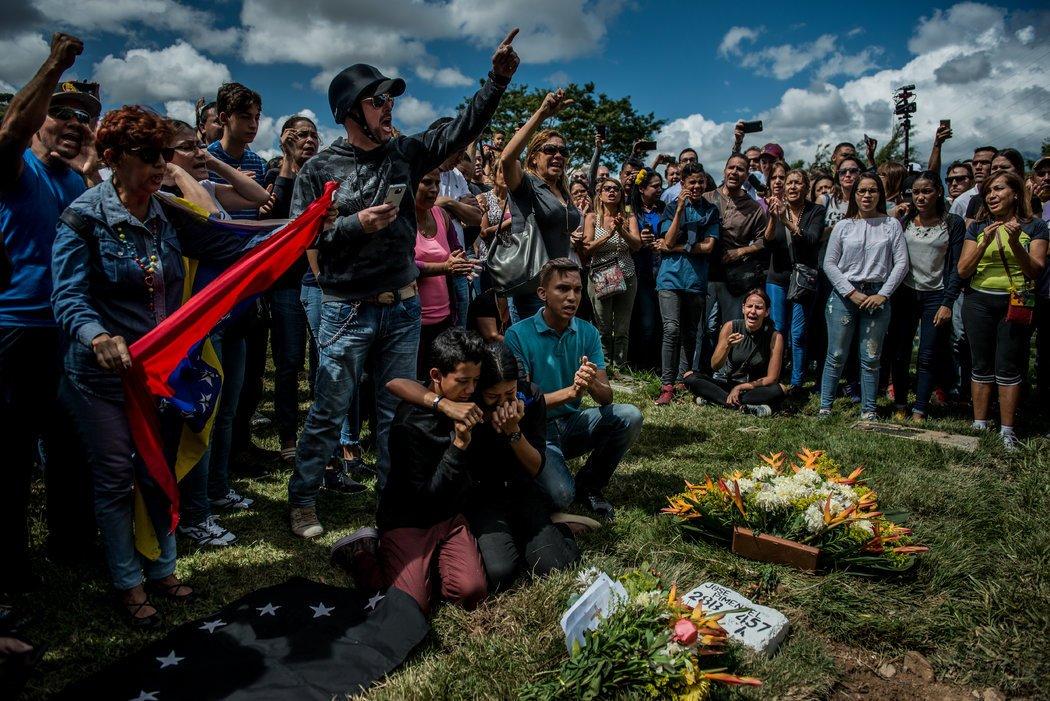 Nicol Díaz, de 17 años, a la derecha, y José Díaz, de 13, al centro, lloran sobre la tumba de su padre, José Alejandro Díaz Pimentel, un rebelde asesinado junto con Pérez en un enfrentamiento con fuerzas gubernamentales. Credit Meridith Kohut para The New York Times