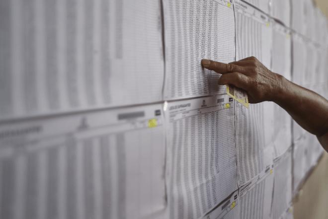 Un hombre revisa el censo electoral en una mesa electoral en Cali, departamento del Valle del Cauca, durante las elecciones parlamentarias en Colombia el 11 de marzo de 2018. Luis ROBAYO / AFP
