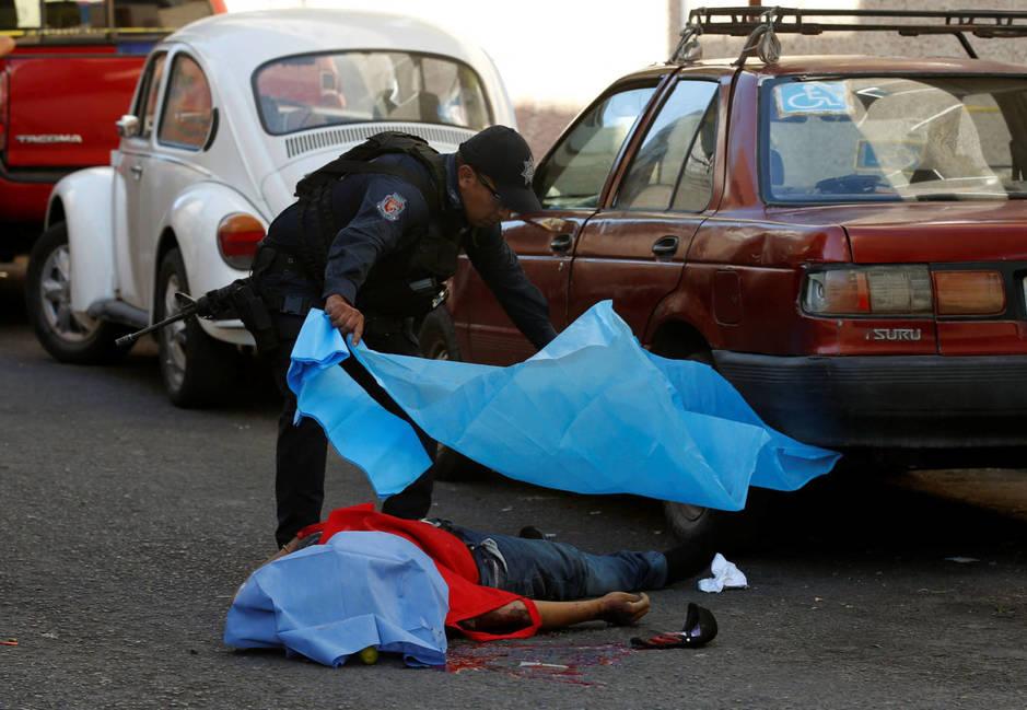 Un policía cubre el cadáver de un hombre asesinado por asaltantes desconocidos en Chilpancingo, Guerrero, el 15 de noviembre de 2017. (Reuters)