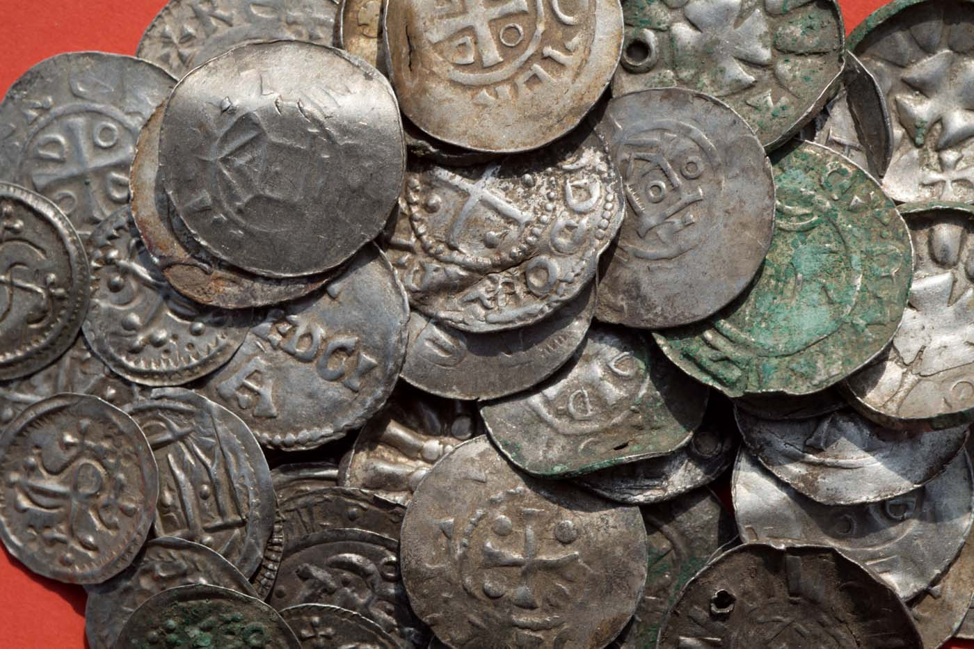 "Saxon, Ottonian, Danish and Byzantine coins are pictured on a table in Schaprode, northern Germany on April 13, 2018. A 13-year-old boy and a hobby archaeologist have unearthed a ""significant"" trove in Germany which may have belonged to the legendary Danish king Harald Bluetooth who brought Christianity to Denmark. A dig covering 400 square metres (4,300 square feet) that finally started over the weekend by the regional archaeology service has since uncovered a trove believed linked to the Danish king who reigned from around 958 to 986. Braided necklaces, pearls, brooches, a Thor"