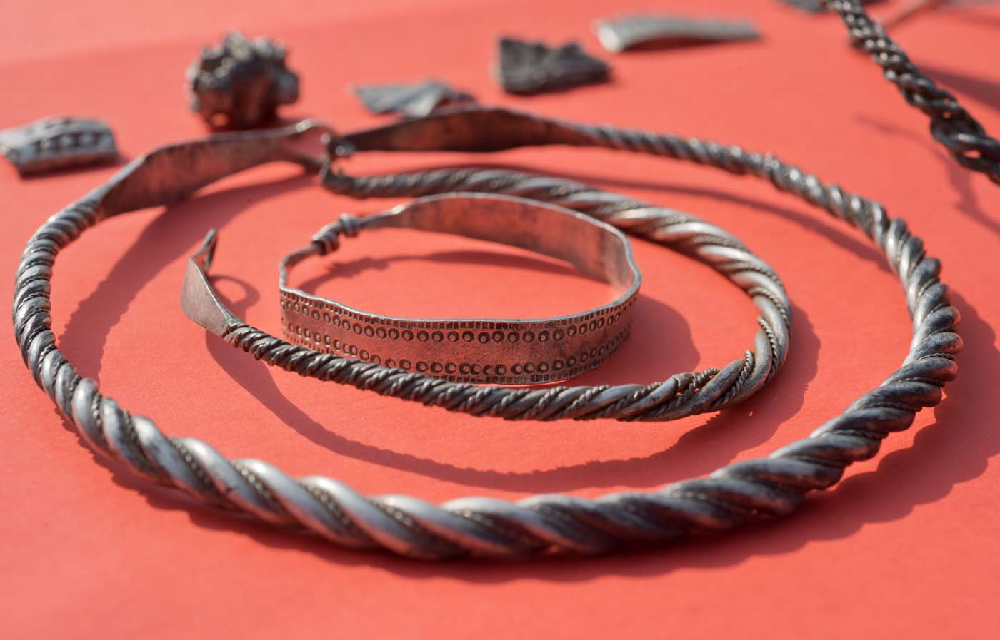 "Parts of the silver treasure are pictured on a table in Schaprode, northern Germany on April 13, 2018. A 13-year-old boy and a hobby archaeologist have unearthed a ""significant"" trove in Germany which may have belonged to the legendary Danish king Harald Bluetooth who brought Christianity to Denmark. A dig covering 400 square metres (4,300 square feet) that finally started over the weekend by the regional archaeology service has since uncovered a trove believed linked to the Danish king who reigned from around 958 to 986. Braided necklaces, pearls, brooches, a Thor"