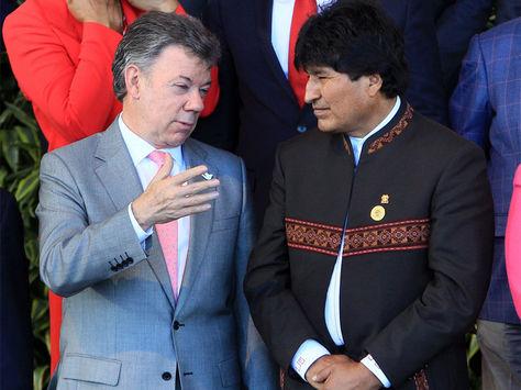 El presidente de Colombia, Juan Manuel Santos (i), habla con su homólogo de Bolivia, Evo Morales (d), durante la foto oficial de la III Cumbre de la Comunidad de Estados Latinoamericanos y Caribeños (CELAC).