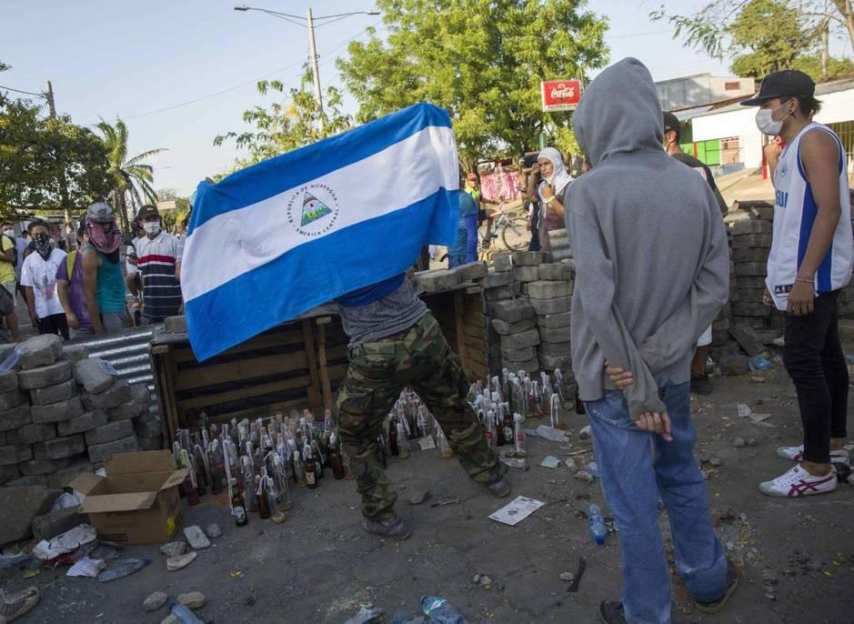 Varios jóvenes protestan el domingo durante el quinto día de manifestaciones en contra de una reforma a la seguridad social, en Managua, Nicaragua. (EFE)