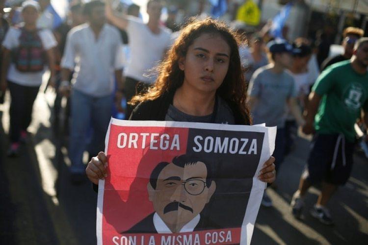 Una manifestante marcha con un cartel que compara al presidente Daniel Ortega con el dictador Anastasio Somoza (REUTERS/Jorge Cabrera)