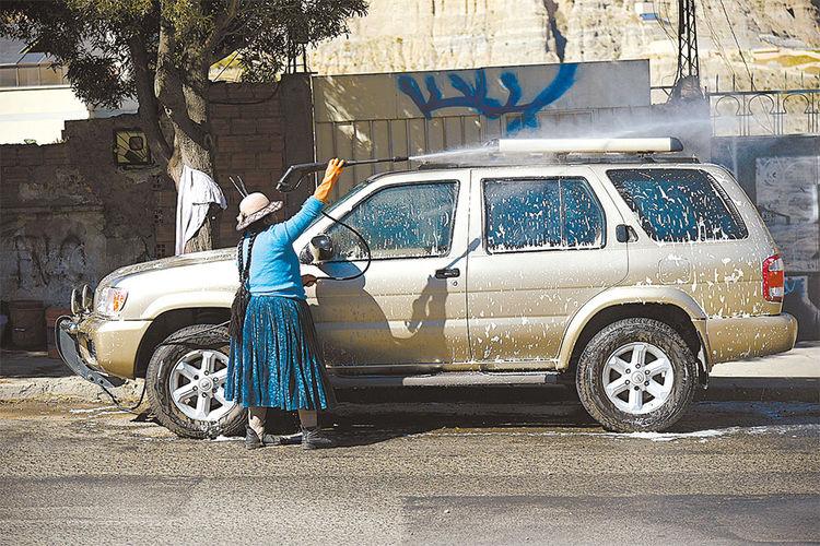 Trabajo. Una mujer hecha agua con manguera sobre un motorizado. Foto:Christian Calderon