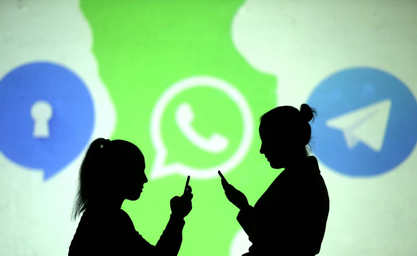 REFILE - CLARIFYING CAPTION Silhouettes of mobile users are seen next to logos of social media apps Signal, Whatsapp and Telegram projected on a screen in this picture illustration taken March 28, 2018.  REUTERS/Dado Ruvic/Illustration