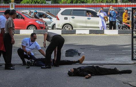 Los espectadores toman fotos mientras la policía examina los cuerpos de dos atacantes después de lanzar un ataque contra la sede de la policía en Pekanbaru. Foto: AFP