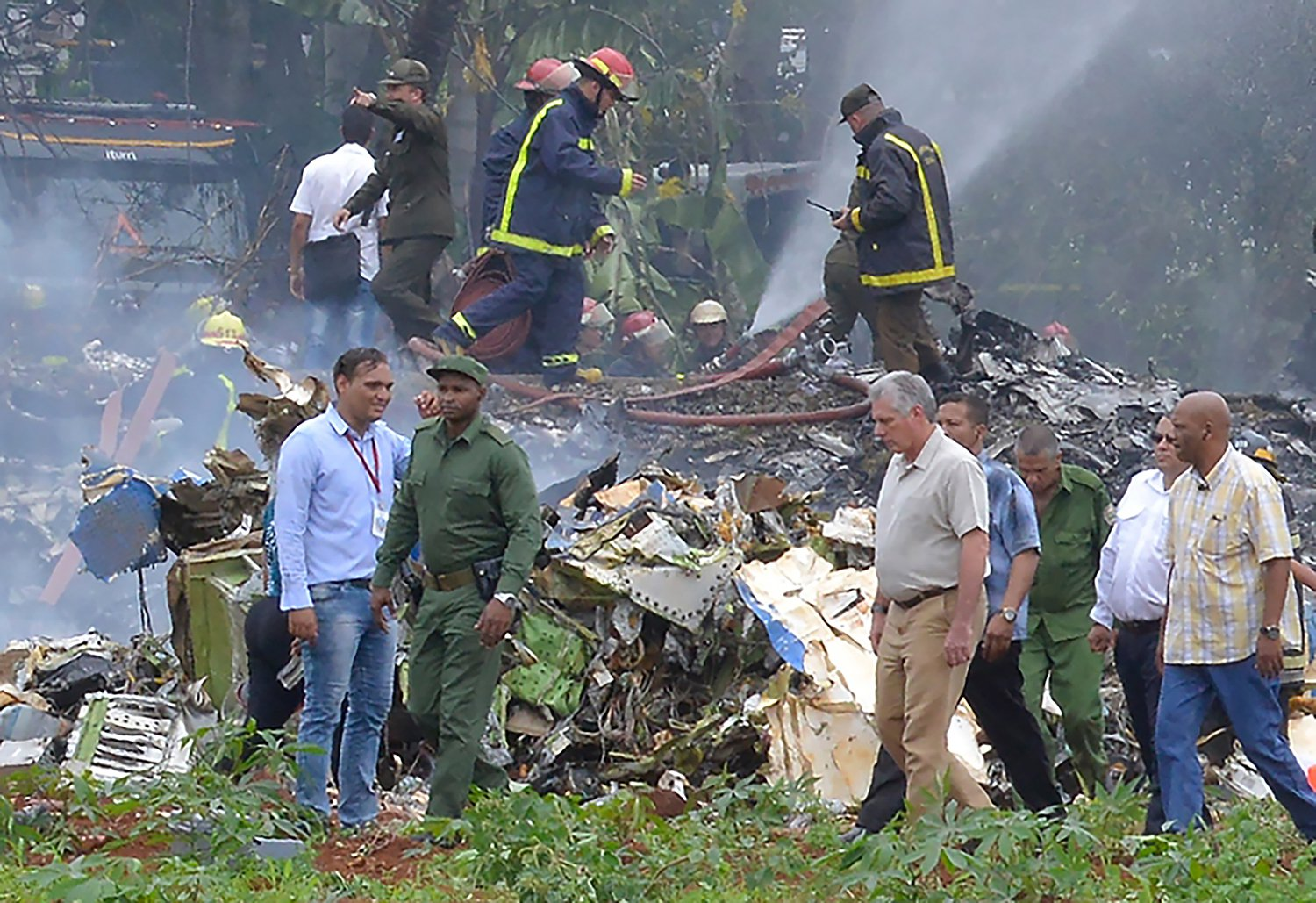 Cuban President Miguel Diaz-Canel (2-R, in khaki) is pictured at the site of the accident after a Cubana de Aviacion aircraft crashed after taking off from Havana