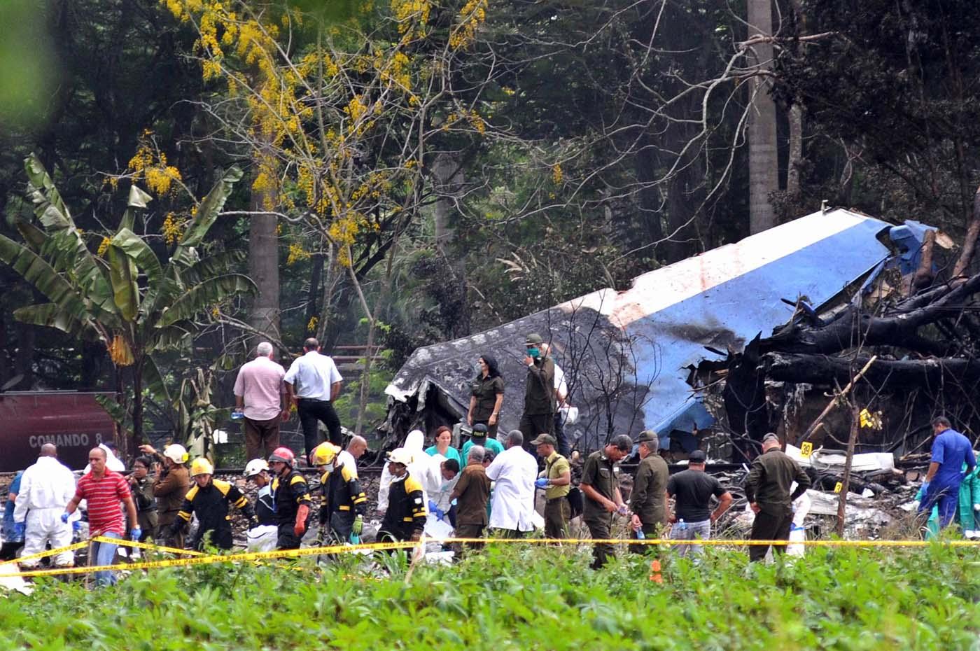 """HAB32. LA HABANA (CUBA), 18/05/2018.- Policías y militares trabajan entre los restos del avión Boeing-737 que se estrelló hoy, viernes 18 de mayo de 2018, poco después de despegar del aeropuerto José Martí de La Habana (Cuba). La mayoría de las más de cien personas que murieron hoy al estrellarse un avión cerca del aeropuerto de La Habana eran cubanos, a excepción de cinco pasajeros extranjeros cuya nacionalidad aún se desconoce y de miembros de la tripulación, que eran mexicanos. Según los medios estatales cubanos, tras la confusión inicial sobre las nacionalidades de las víctimas """"quedó confirmado que la mayoría de los pasajeros eran cubanos, excepto unos cinco extranjeros y la tripulación"""". EFE/Omara García"""