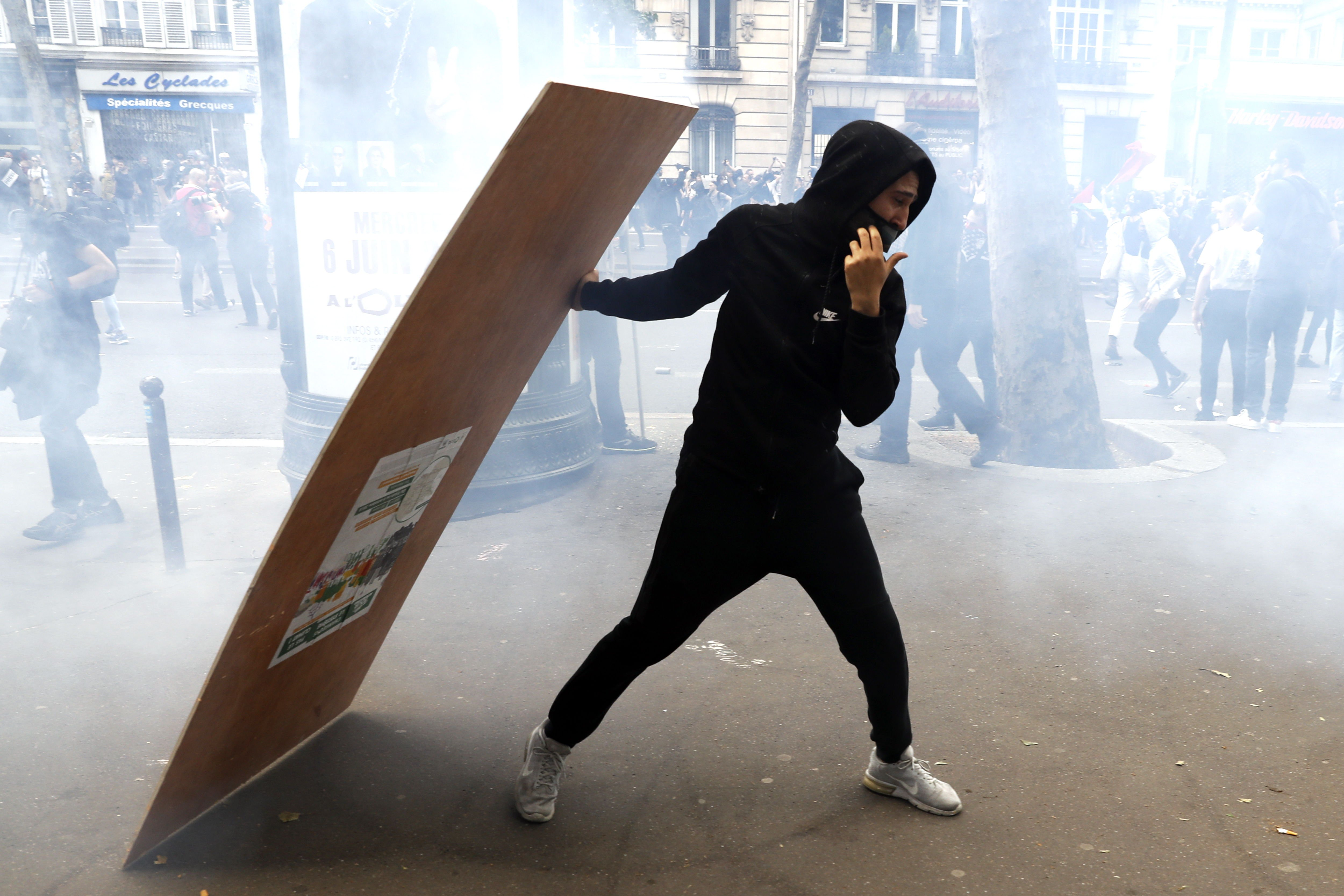 Paris (France), 26/05/2018.- A protester takes cover behind a wooden plank as clashes erupt with the police during a demonstration against French government reforms in Paris, France, 26 May 2018. Far left political parties and French trade union CGT (General Confederation of Labour) call for a national day of protest against the government policies. (Protestas, Francia) EFE/EPA/ETIENNE LAURENT