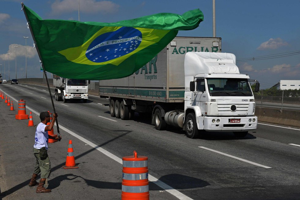 La huelga de camioneros brasileños contra el aumento del precio del diésel comenzó a perder fuerza después de ocho días de bloqueos que paralizaron a la mayor economía de América Latina y sacudieron a su impopular gobierno. En la imagen, un manifestante con la bandera nacional de Brasil en el exterior de unarefinería en Río de Janeiro, el 28 de mayo de 2018.