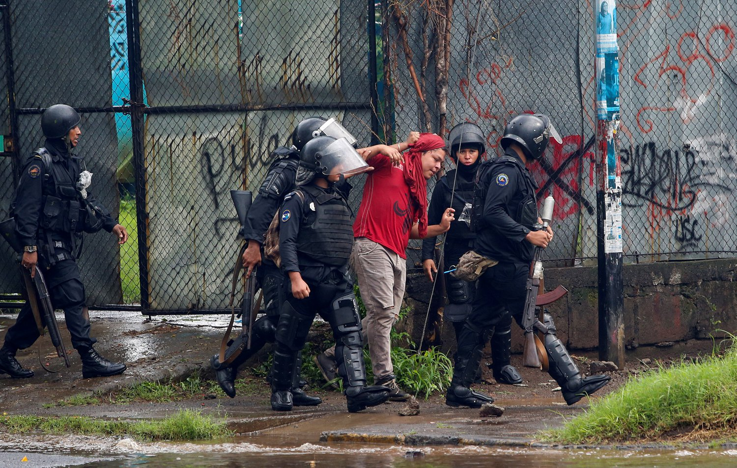 Riot police officers detain a demonstrator during a protest against Nicaragua