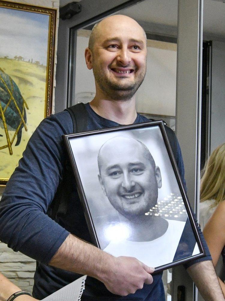 Babchenkocon el retrato que sus compañeros habían colgado en la redacción del canalATR TV tras la noticia de su muerte (AFP / Genya SAVILOV)