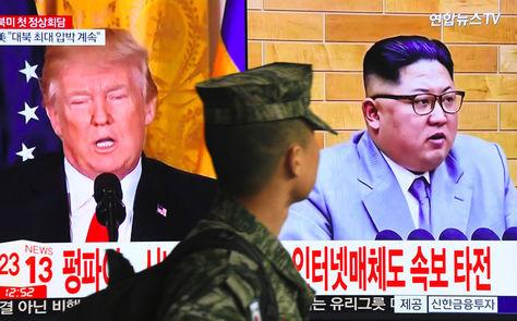 Un soldado surcoreano pasa frente a una pantalla de televisión que muestra imágenes del presidente Donald Trump (izq.) y el líder norcoreano, Kim Jong Un, en una estación de tren en Seúl. Foto: AFP