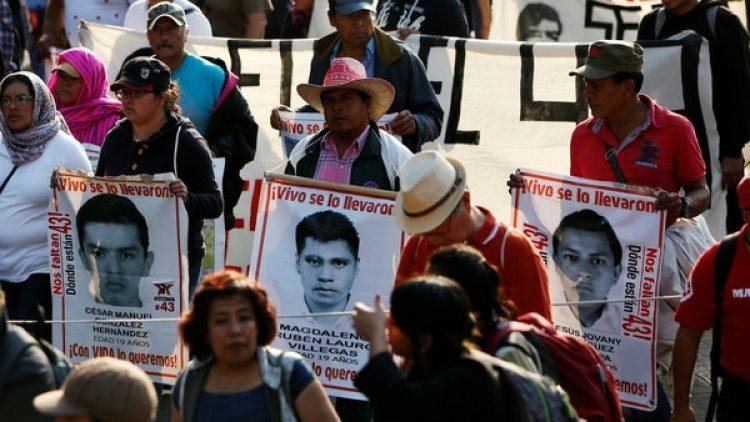 Parientes de los 43 estudiantes de Ayotzinapa durante una marcha para recordar el mes número 29 desde la desaparición de los jóvenes, este domingo en Ciudad de México (Reuters)
