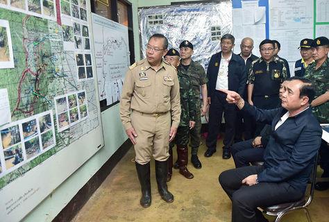 El primer ministro tailandés, Prayut Chan-o-cha (d), observa un mapa de la cueva de Tham Luang a fin de seguir la investigación de cerca. Foto: EFE