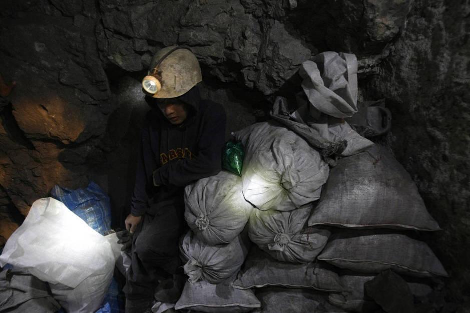Moisés, un joven minero de 17 años, guarda sacas de mineral en la mina de El Rosario en Cerro Rico, en enero de 2010. (Reuters)