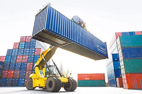 Comercio. Un montacargas para contenedores manipula un vagón con mercadería.