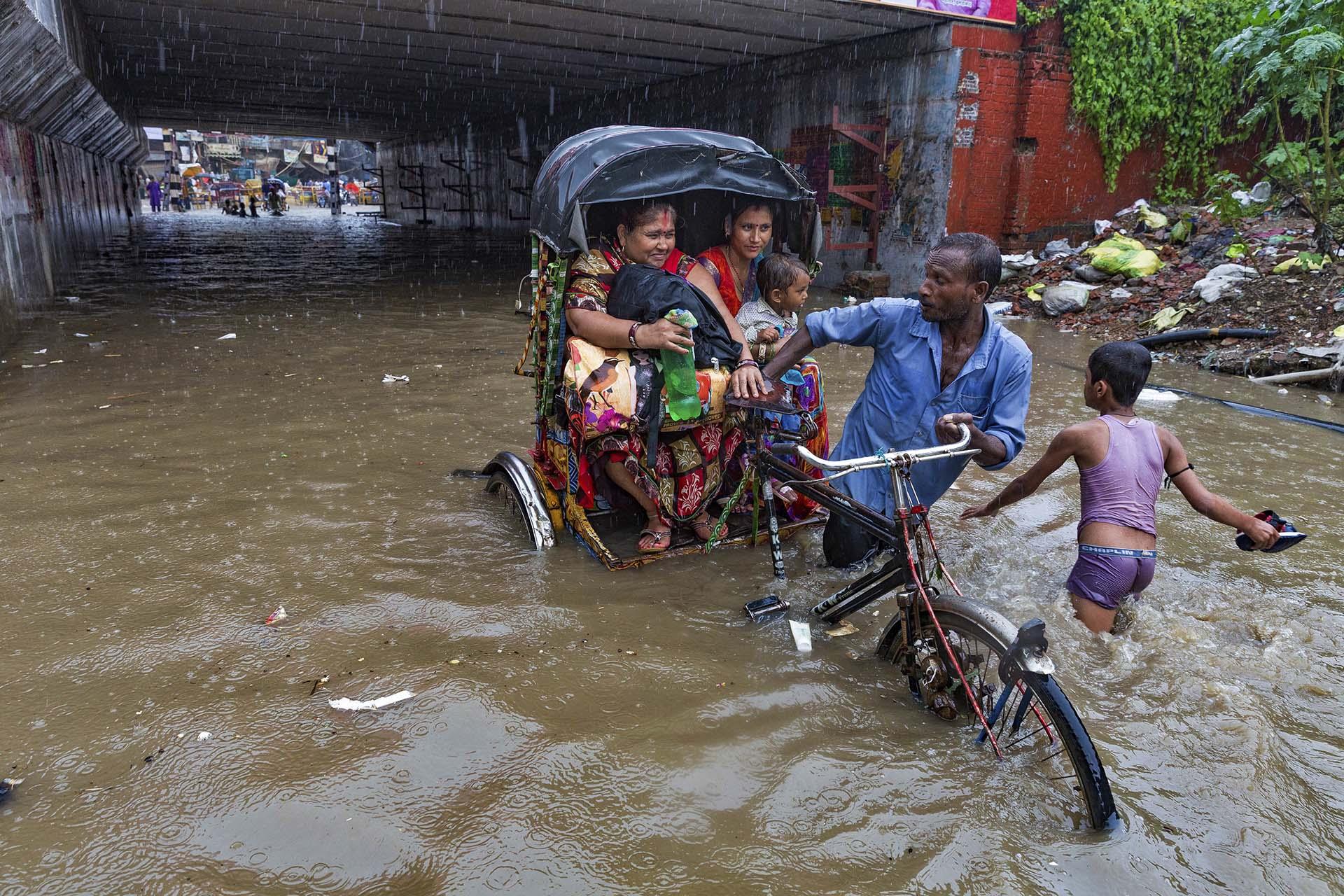 Un hombre transporta a dos mujeres en medio del temporal(AP Photo/Rajesh Kumar Singh)