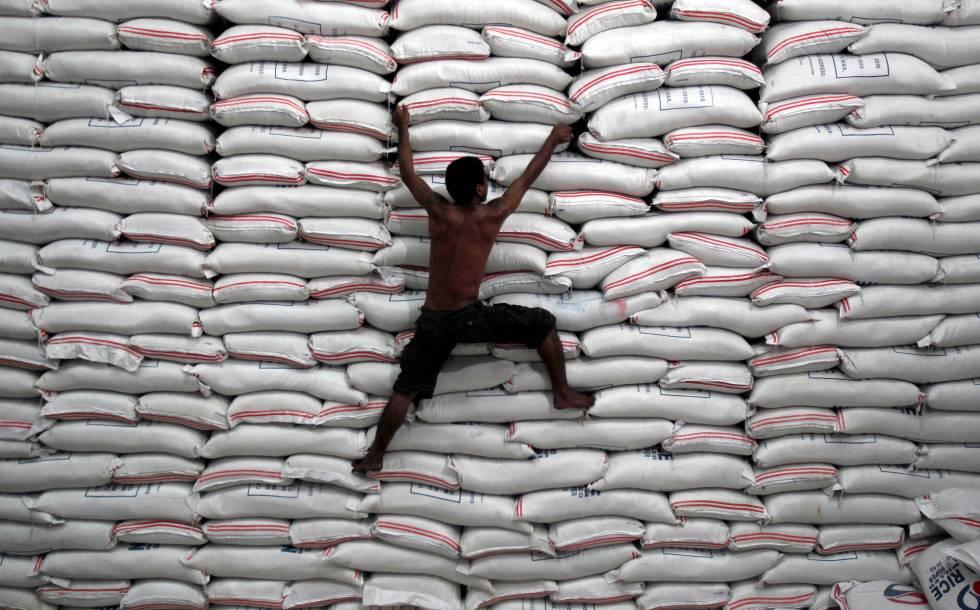 Un hombre trepa por unos sacos de arroz en un almacén gubernamental de Filipinas.