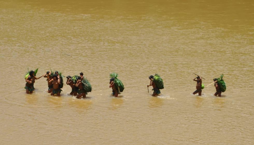 Un grupo de indígenas en aislamiento cruza un río en departamento de Madre de Dios, en Perú. Si tuvieran una afección, habría de ser atendidos en la orilla.rn rn