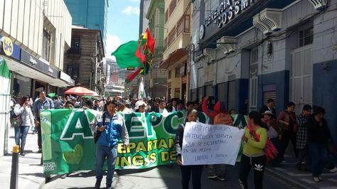 Los afiliados de Adepcoca marchan por una de las vías del centro de La Paz para exigir la liberación de sus compañeros.